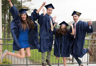 Four female and male students jumping on the bridge in the graduation caps and gowns.