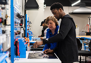 African American student receiving help on a machine from his Mechatronics professor