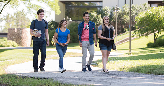 Four students walking on main campus