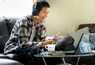 Smiling student wearing headphones while watching a webinar on their laptop