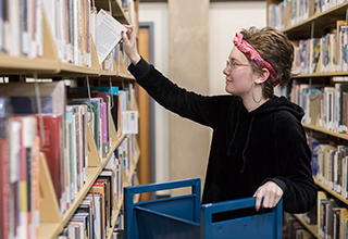 Student worker in the Rock Valley College Library places books on a shelf